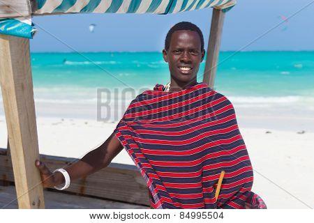 Traditonaly dressed black man on beach.