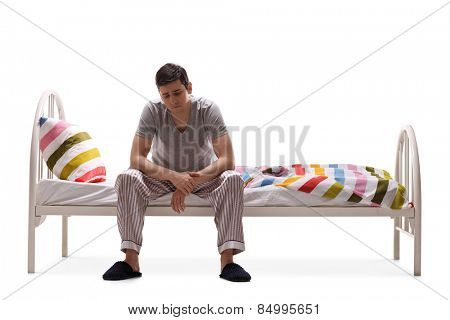Sad man in pajamas sitting on a bed isolated on white background