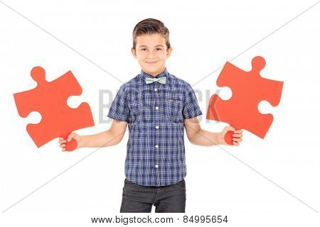 Kid holding two pieces of a puzzle isolated on white background