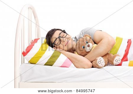 Childish young man sleeping with a teddy bear isolated on white background