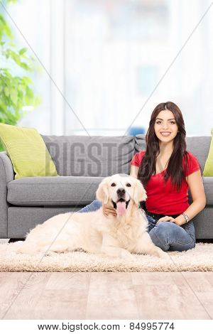 Vertical shot of a young woman sitting by a sofa with her dog at home