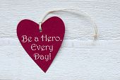 stock photo of heroes  - One Red Heart Label Or Tag With White Ribbon On White Wooden Background With English Text Be A Hero Every Day Vintage Retro Or Rustic Style - JPG