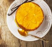image of testis  - Home made whole testy orange cake with honey glaze and natural vanilla on wooden background - JPG