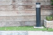 foto of lamp post  - Lamp post against a textured wood wall - JPG