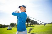 stock photo of ladies golf  - Lady golfer teeing off and smiling on a sunny day at the golf course - JPG