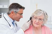 stock photo of ear  - Doctor examining female patients ear with otoscope in clinic - JPG