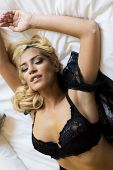 stock photo of laying-in-bed  - Pretty young woman laying on the bed - JPG