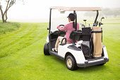 stock photo of buggy  - Golfer driving in his golf buggy in golf course - JPG