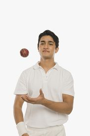 stock photo of cricket shots  - Bowler tossing a cricket ball - JPG