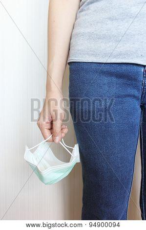 Female's Hand Holding Medical Mask
