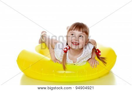 Happy joyful blonde girl with pigtails is on a yellow inflatable
