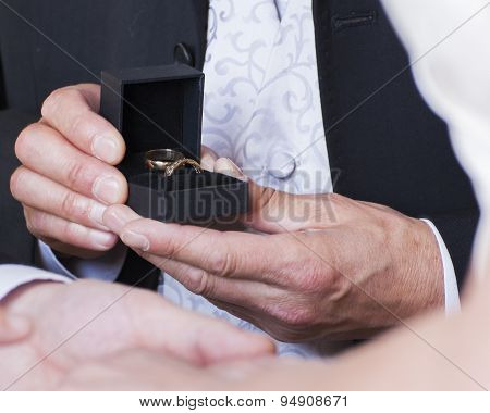 Best Man Presenting Rings To Bride And Groom