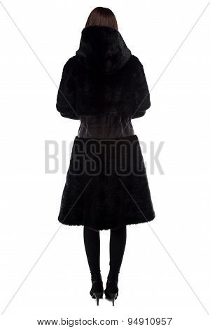 Brunette in black fur coat from back