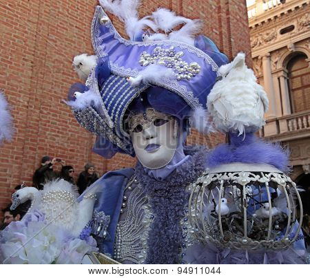 Masked Person In Magnificent Lilac Costume On San Marco Square In Venice, Italy.