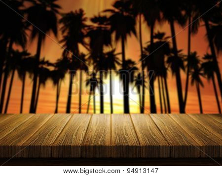 3D render of a wooden table with a defocussed image of palm trees at sunset