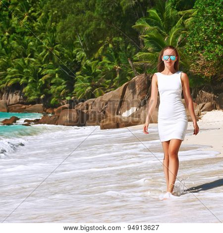 Woman wearing dress on beach Anse Intendance at Seychelles, Mahe