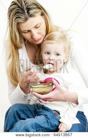 portrait of mother feeding her little daughter