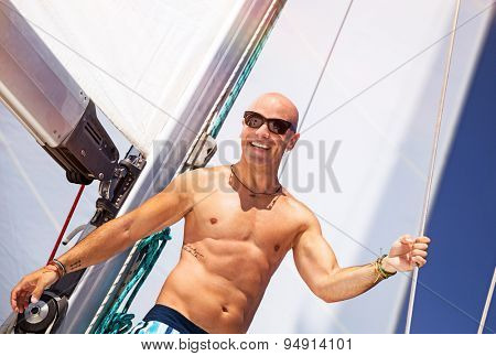 Happy smiling man having fun on sailboat, beautiful shirtless sportive sailor with stylish tattoo enjoying active summer adventure, luxury beach holidays