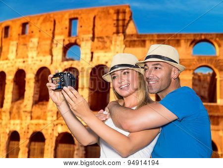 Beautiful couple taking picture of themselves on Coliseum background, happy young family spending summer vacation in Rome, Italy, Europe