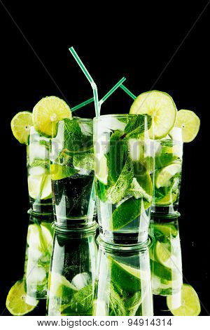 Mojito cocktails with lime and mint on black background