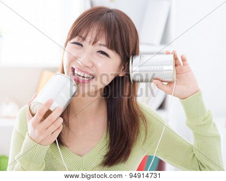 Happy Asian girl using old technology, talk and listen to communication cans. Young woman indoors living lifestyle at home.