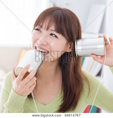 Asian girl using old technology, talk and listen to communication cans. Young woman indoors living lifestyle at home.