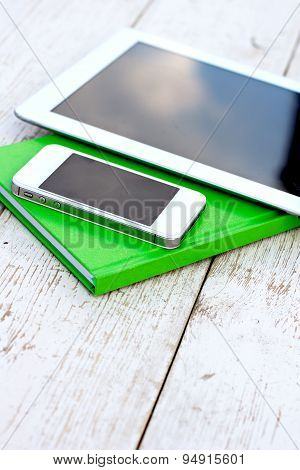 Notebook and  mobile phone  on a wooden table