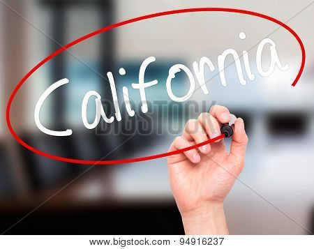 Man Hand writing California with black marker on visual screen.