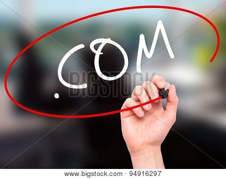 Man Hand writing .COM with black marker on visual screen.