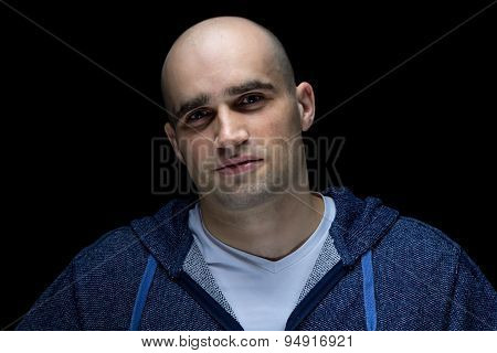 Photo of smiling hairless man in shadow