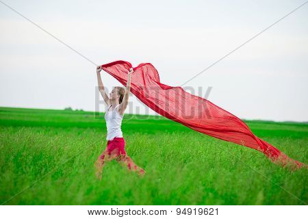 Young lady runing with tissue in green field. Woman and red scarf.