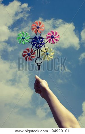 Hand Hold Pinwheel On Blue Sky Background