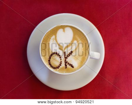 Coffee Cup With Milk And Ok Shape On Red Background