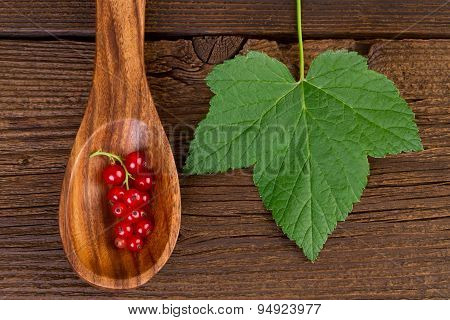 redcurrant in wooden spoon and leaf on wooden background