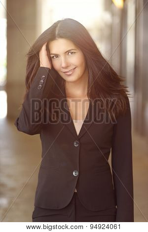 Brunette Businesswoman Outdoors With Hand In Hair