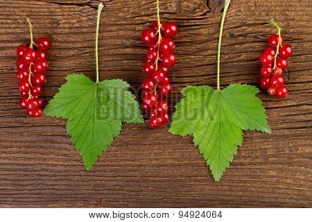 redcurrant berries and leaves over old wooden background