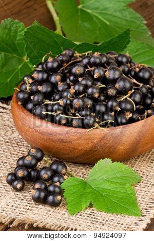 blackcurrant berries in wooden bowl on burlap background
