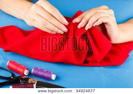Seamstress is sewing cloth herself.