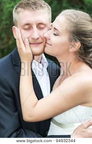 Bride and groom pressed cheeks