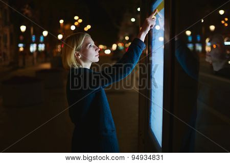 Beautiful female using city computer for touristic information while standing at night city