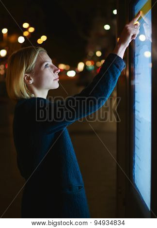 Cropped image with young beautiful woman touching big digital screen of smart bus stop in Barcelona
