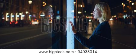 Woman verifies account balance on banking application via modern device standing in night city