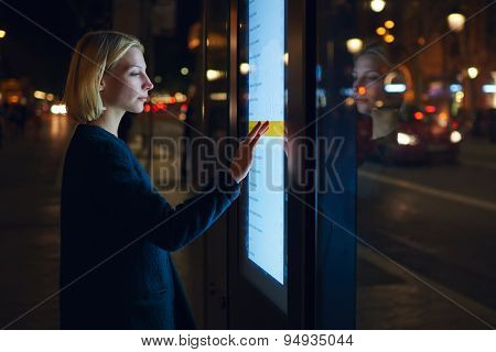Girl touching sensitive screen while selecting option on the list for find out schedule of transport