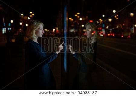 Attractive young woman consults on modern big timetable outdoors with beautiful lights on background
