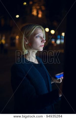 Portrait of caucasian young woman strolling in night city  while holding mobile phone in the hand