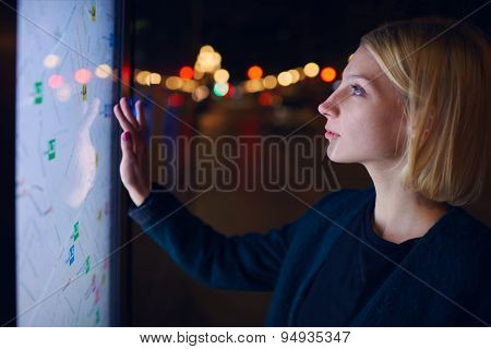 Female tourist using smart city gadget to get direction in Barcelona central, female in night city