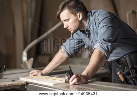 Young Carpenter Using Measuring Tape