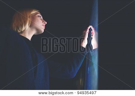 Blonde hair caucasian female touching big digital display with reflected on her screen light