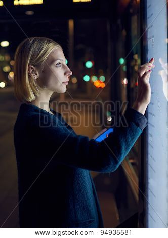 Blonde female touching sensitive display for tourist information with urban help technology system