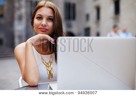 Charming woman sitting at street coffee shop with open netbook while looking to you